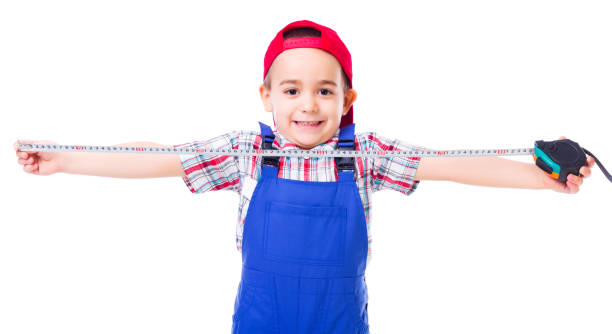 Little handyman with measuring tape stock photo