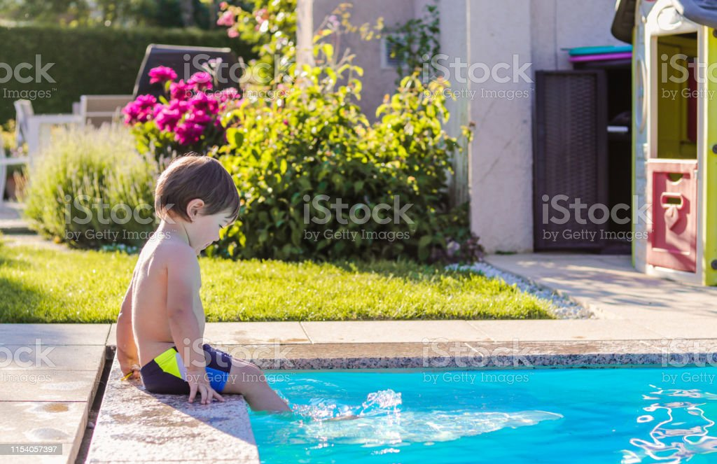 Little happy boy sitting on side of swimming pool in garden playing...