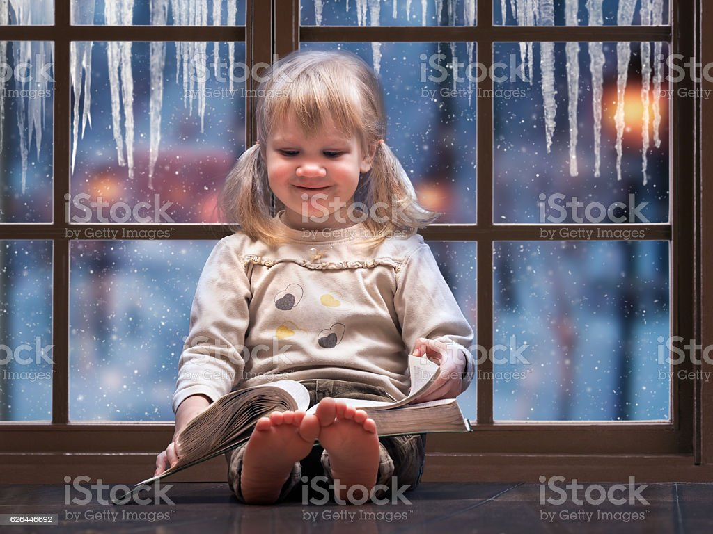 Little happy child reading a book. стоковое фото