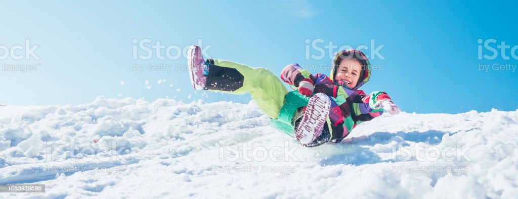 Glückliches Mädchen gleitet nach unten aus dem Schneehang mit blauem Himmelshintergrund – Foto