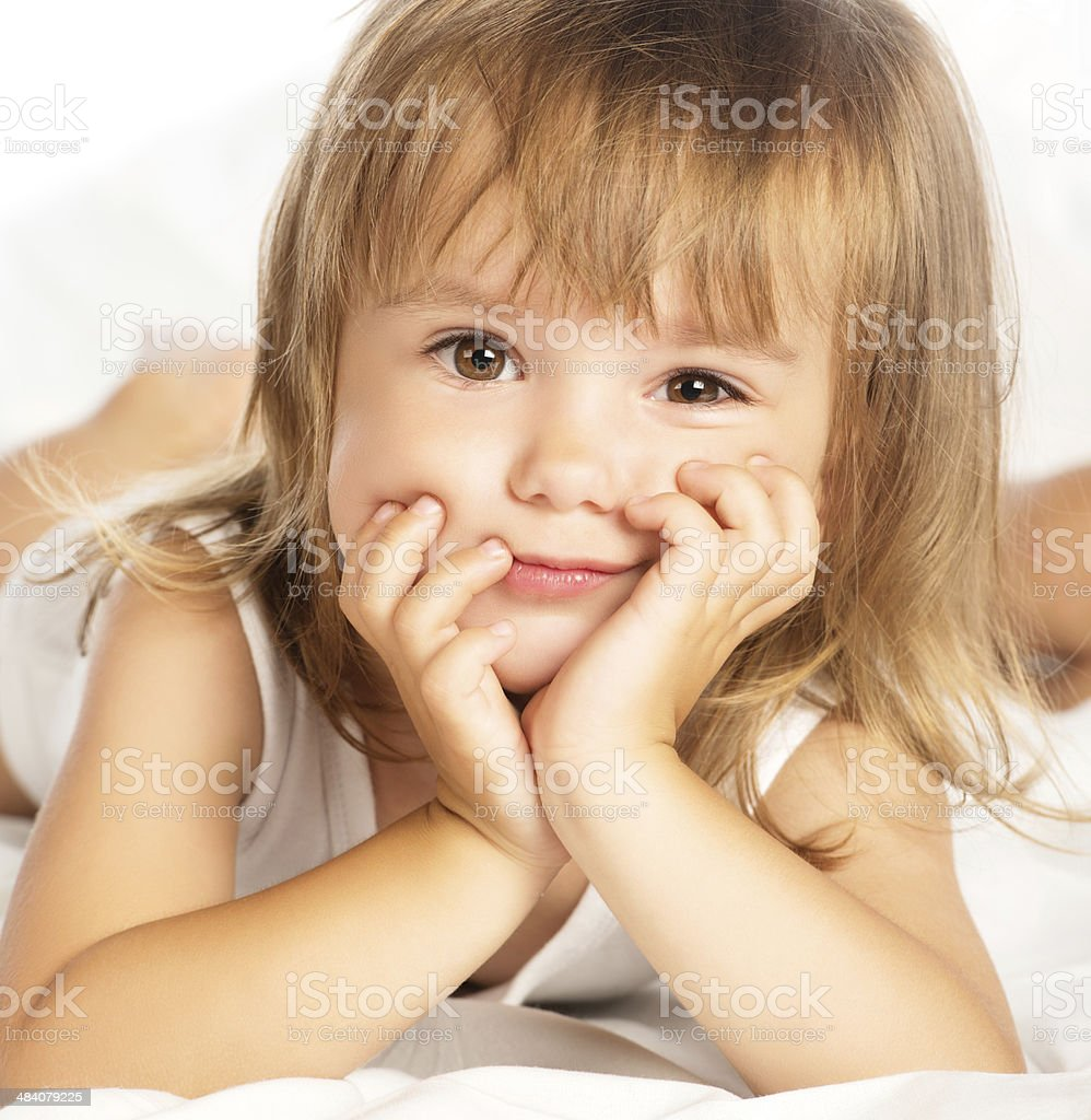little happy smiling cheerful girl in a bed isolated royalty-free stock photo