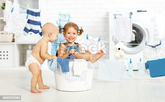 954356678istockphoto little helpers funny kids happy  in laundry to wash clothes, playing and laughing 666593360