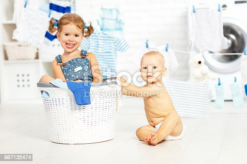 954356678istockphoto little helpers funny kids happy  in laundry to wash clothes, playing and laughing 667135474