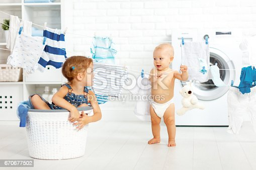 954356678istockphoto little helpers funny kids happy  in laundry to wash clothes, playing and laughing 670677502