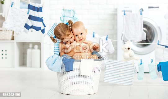 954356678istockphoto little helpers funny kids  in laundry to wash clothes, playing and laughing 666593456