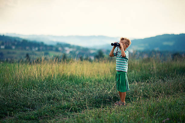 little hiker looking at view with binoculars - binocular boy bildbanksfoton och bilder