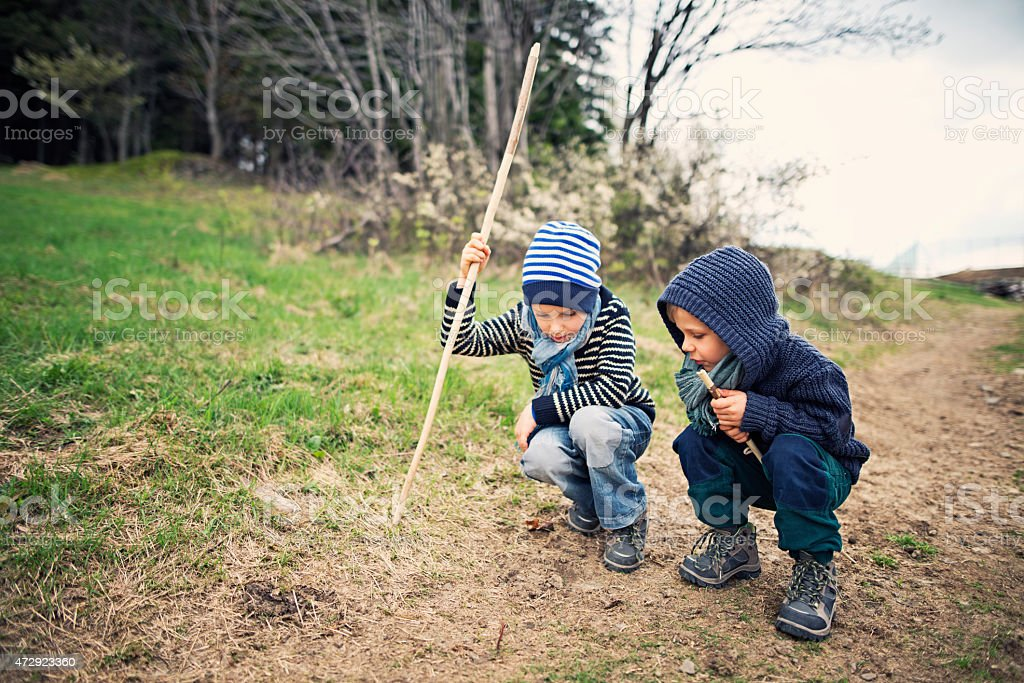 Little hikers observing an earthworm stock photo