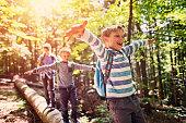 Little hikers walking on a tree trunk  in forest