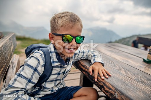 Little boy is hiking on Monte Baldo near Lake Garda, Italy The boy is sitting at outdoors table and resting. Nikon D850
