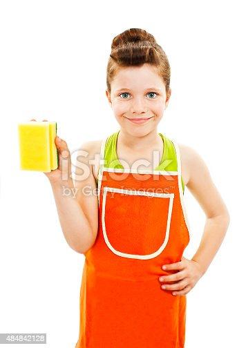 istock Little homemaker in an apron holding a sponge washer 484842128