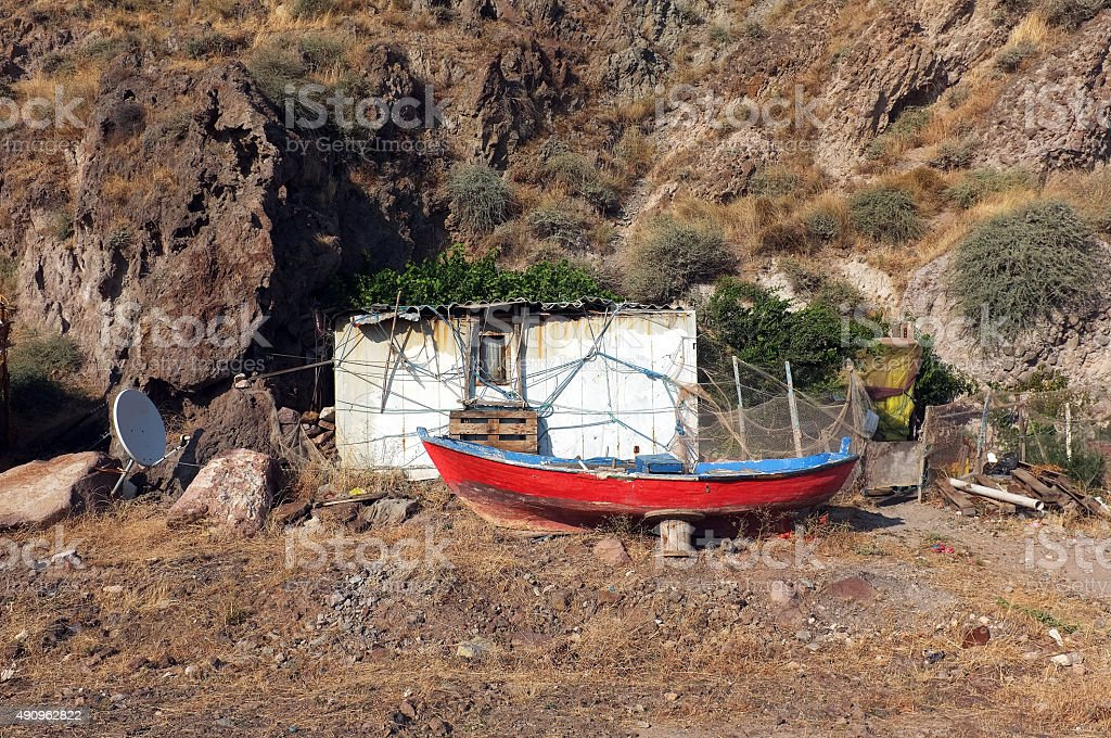 Little hut and a boat in front of hill stock photo