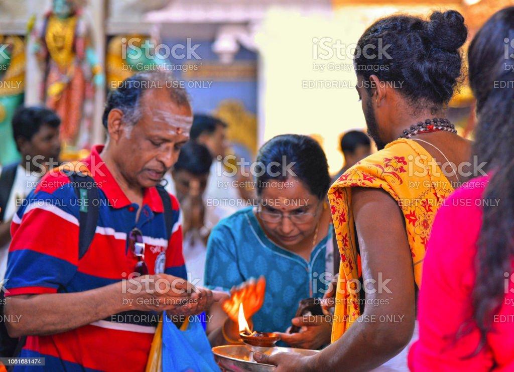 Little India, Singapore People praying at Hindu temple Sri Veeramakaliamman with Brahman priest, burning incense. stock photo