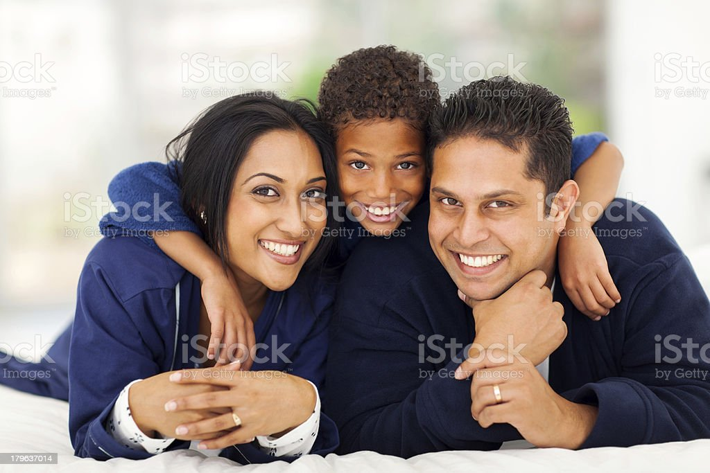 little indian boy hugging his parents on bed stock photo