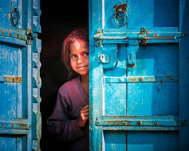 Little indian girl behind a door stock photo