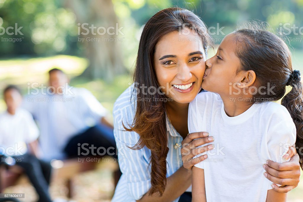 little indian girl kissing her mother stock photo