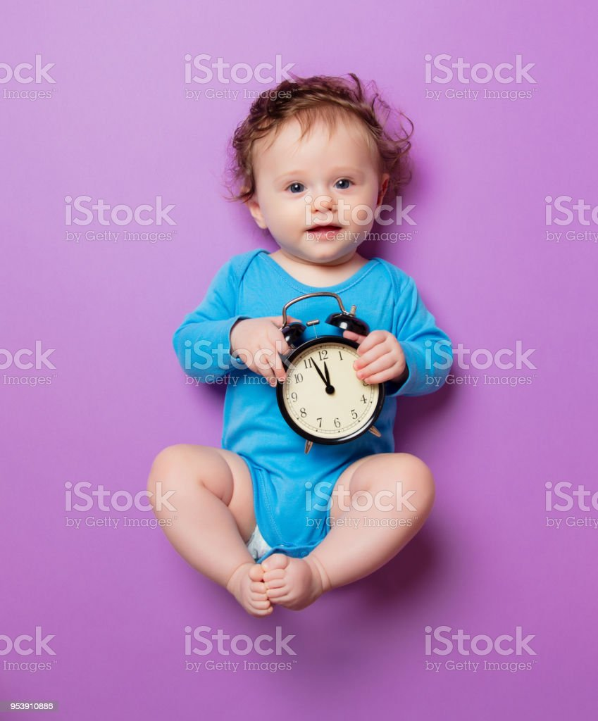 little infant baby with alarm clock stock photo