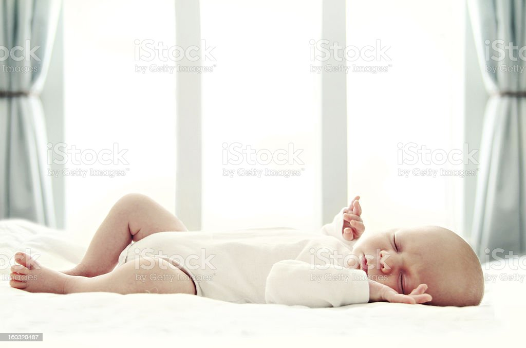 Little infant sleeping on a bed stock photo