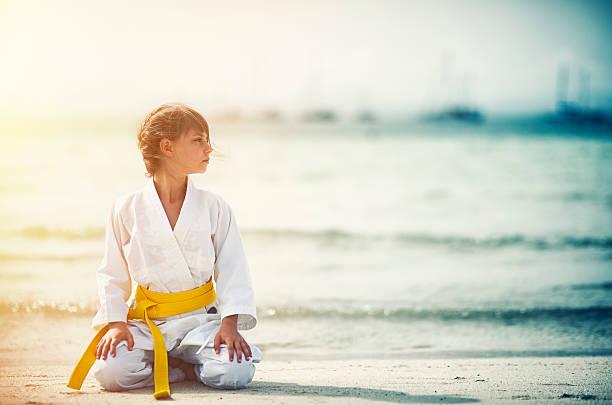 小さな空手座っている女の子 正座 のビーチで - 武道 ストックフォトと画像