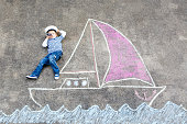 Little kid boy as pirate on ship or sailingboat picture painting with colorful chalks on asphalt.