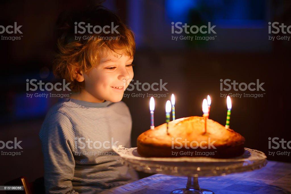 Kleines Kind junge Blasen Kerzen auf Geburtstagskuchen – Foto