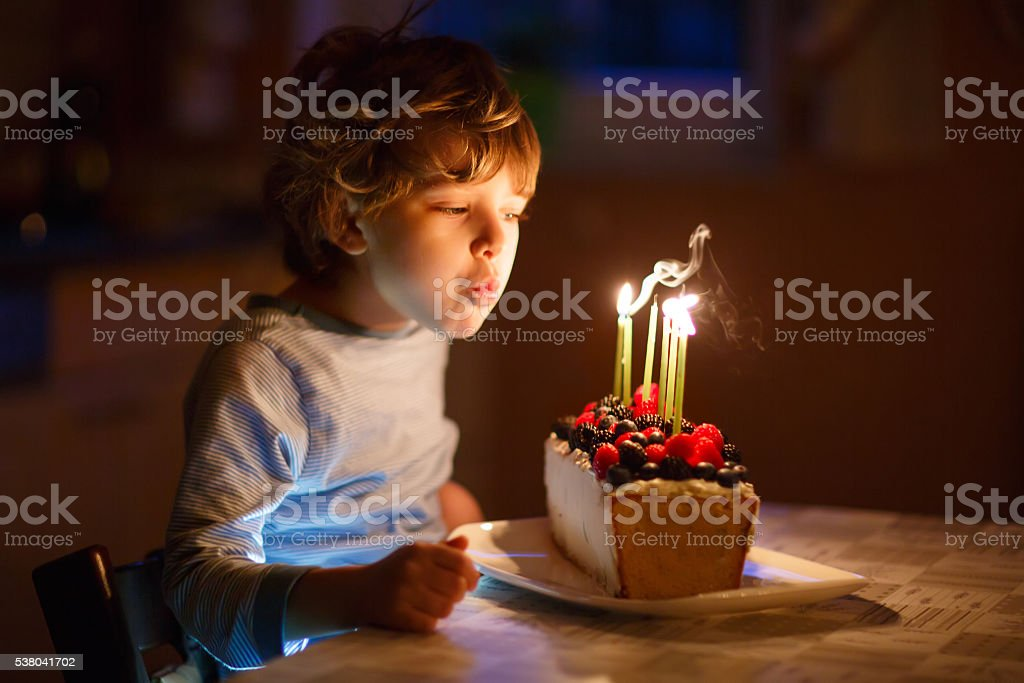 Little kid boy blowing candles on birthday cake stock photo