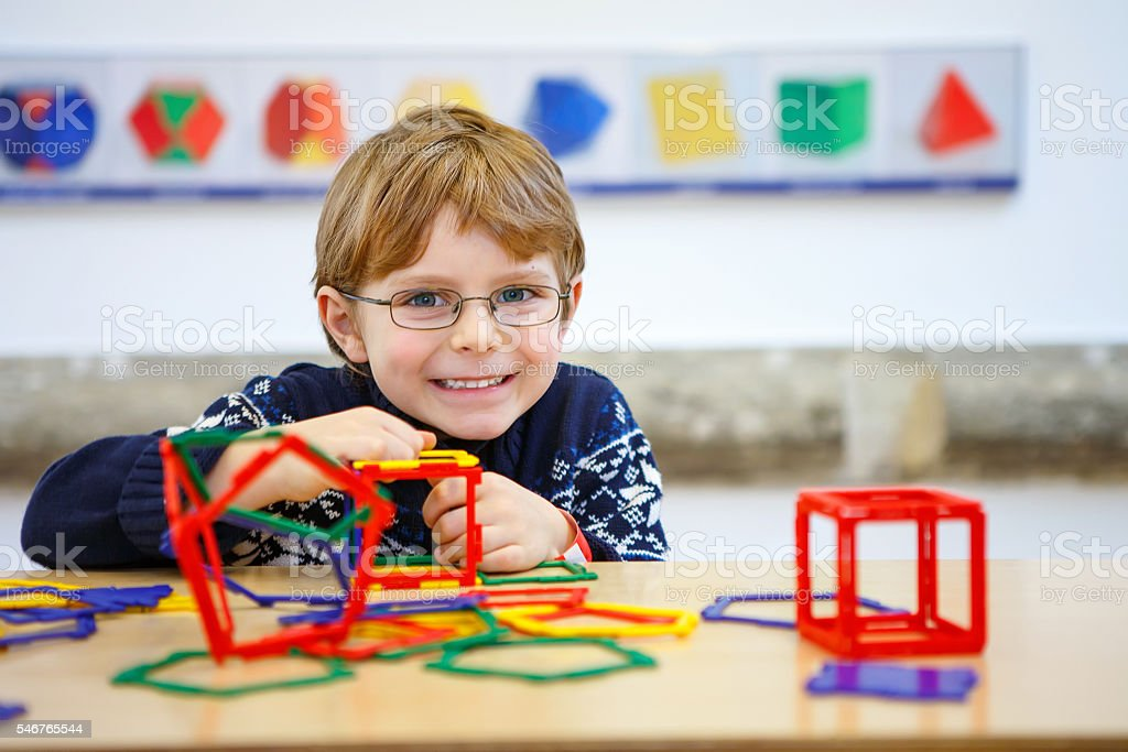 Little kid boy building geometric figures with plastic blocks stock photo