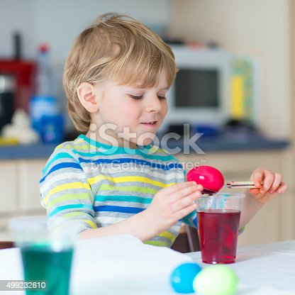 505657693 istock photo Little kid boy coloring eggs for Easter holiday 499232610