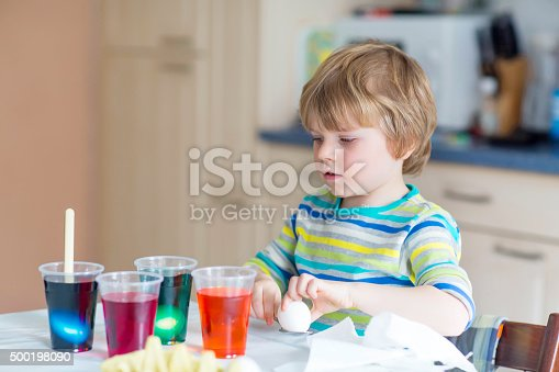 505657693 istock photo Little kid boy coloring eggs for Easter holiday 500198090