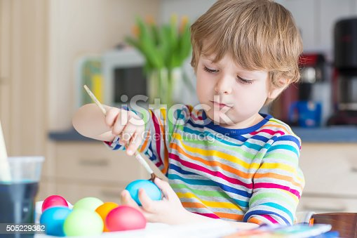 505657693 istock photo Little kid boy coloring eggs for Easter holiday 505229362