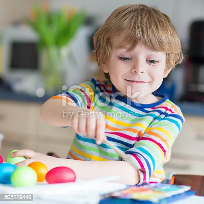 505657693 istock photo Little kid boy coloring eggs for Easter holiday 505229446