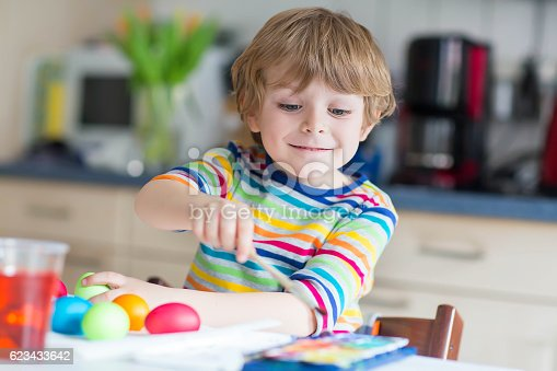 505657693 istock photo Little kid boy coloring eggs for Easter holiday 623433642