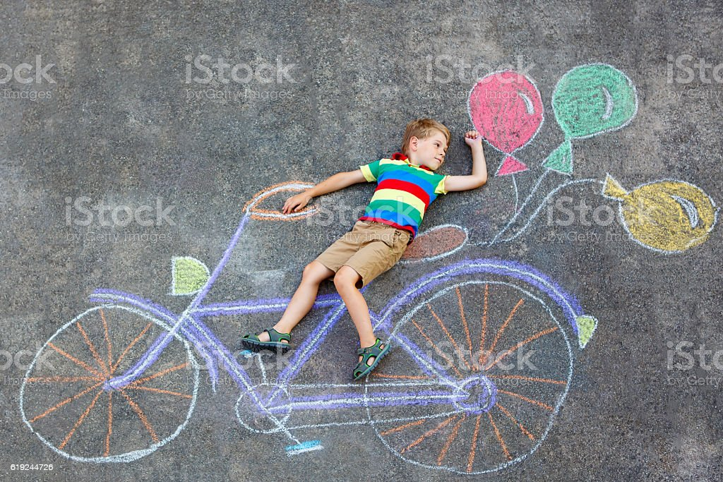 little kid boy drawing bicycle chalks picture on ground stock photo