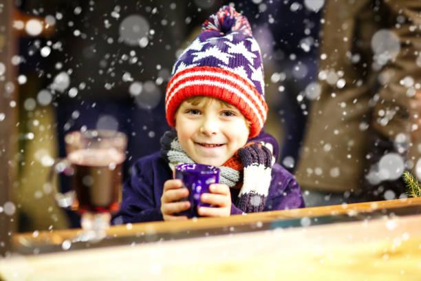 kleine kind junge trinken heißen schokolade auf dem weihnachtsmarkt - vorschuldekorationen stock-fotos und bilder