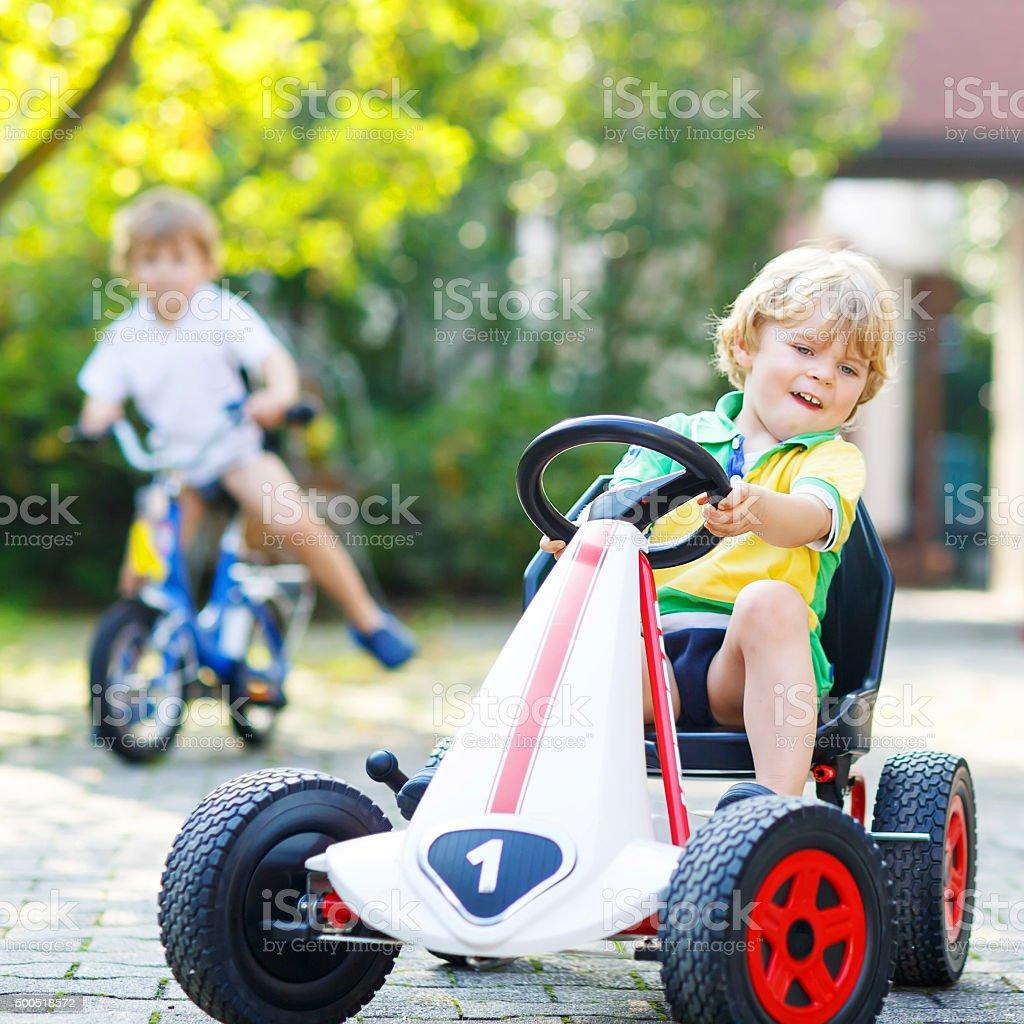 Little kid boy driving pedal car in summer garden stock photo