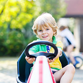 Active blond kid boy driving pedal toy car in summer garden, outdoors. His little brother on bike on background. Active leisure with children.