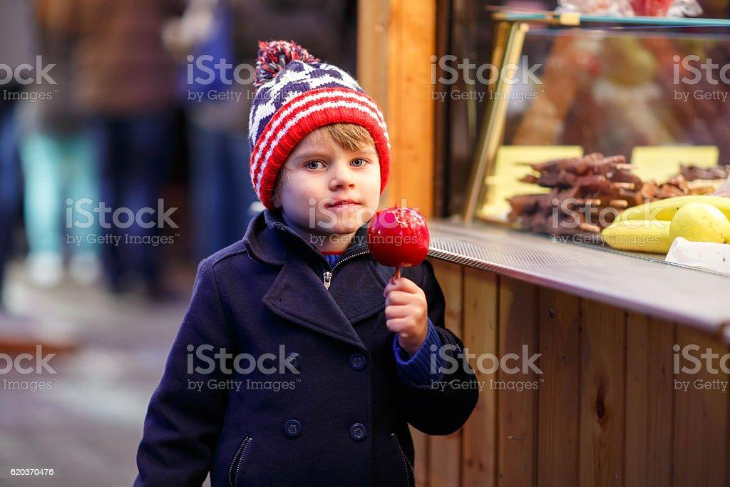 Małe dziecko chłopiec jedzenia Jabłko świątecznych crystalized na rynku zbiór zdjęć royalty-free
