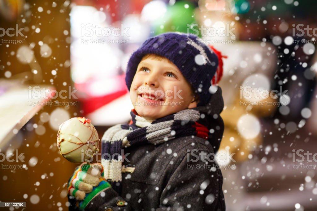 Kleines Kind junge essen Zucker Apfel Süßigkeiten stehen auf Weihnachten mark – Foto