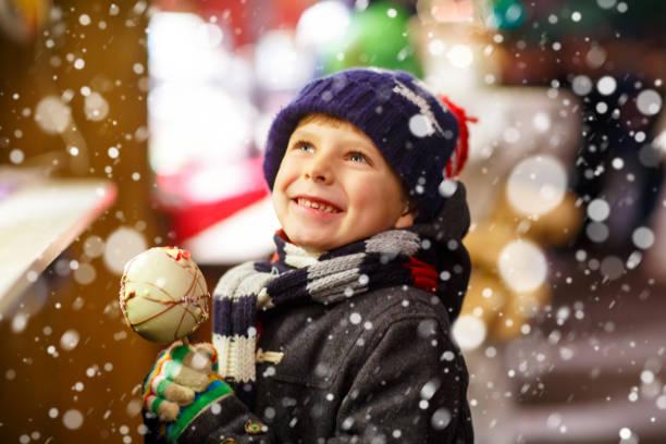 kleines kind junge essen zucker apfel süßigkeiten stehen auf weihnachten mark - vorschuldekorationen stock-fotos und bilder