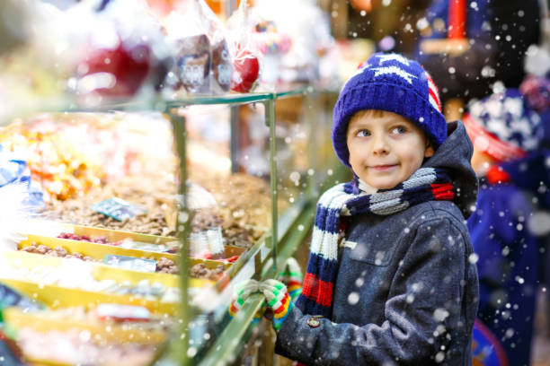 kleines kind junge essen zucker apfel süßigkeiten stehen auf weihnachtsmarkt - vorschuldekorationen stock-fotos und bilder