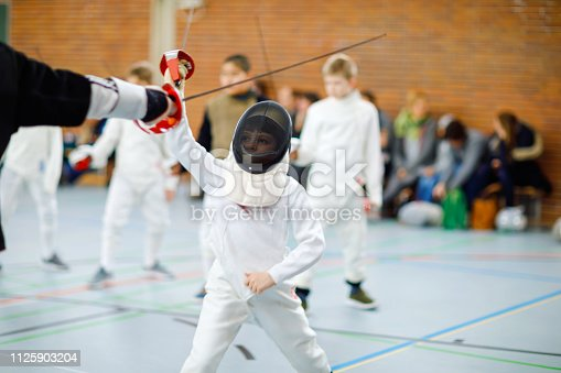 Little kid boy fencing on a fence competition. Child in white fencer uniform with mask and sabre. Active kid training with teacher and children. Healthy sports and leisure