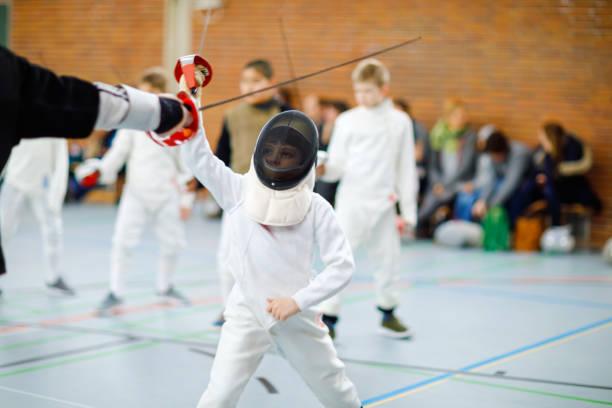 Kleine Kind junge Fechten auf einen Zaun-Wettbewerb. Kind in weißer uniform mit Maske und Säbel Fechter. Aktives Kind training mit Lehrer und Kinder. Gesunder Sport und Freizeit. – Foto