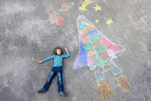 little kid boy flying by a space shuttle chalks picture - chalk drawing stock photos and pictures