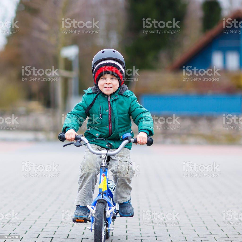 Little kid boy having fun on bicycle outdoors stock photo