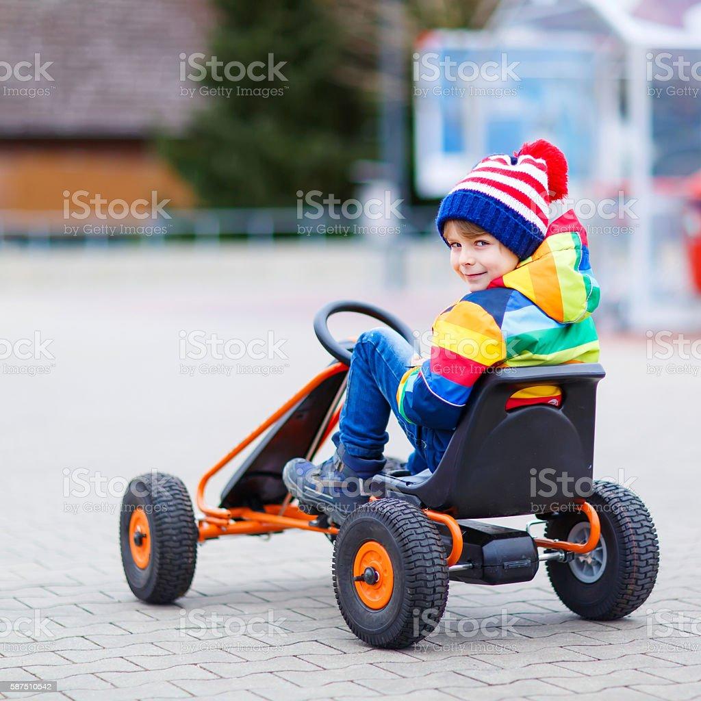 Little kid boy having fun on toy race car outdoors stock photo