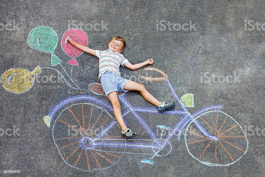 little kid boy having fun with bike chalks picture stock photo