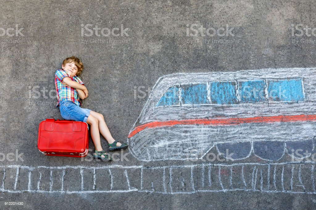 Little kid boy having fun with fast train picture drawing with colorful chalks on asphalt stock photo