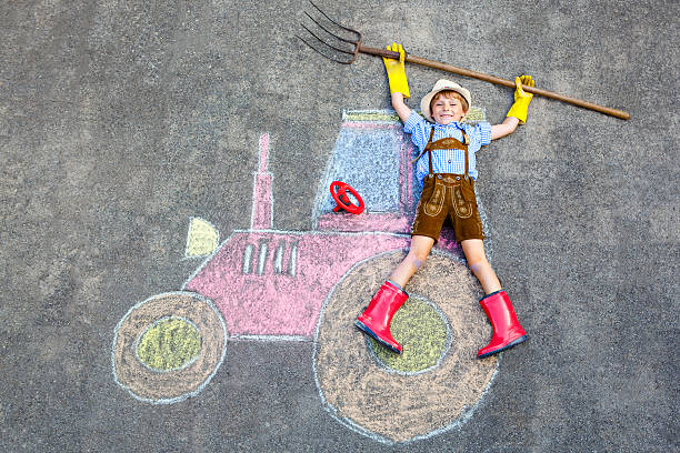 kleines kind junge spaß haben mit traktor chalks bild - malerei schuhe stock-fotos und bilder
