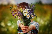 istock Little kid boy holding bouquet of fields flowers. Child giving flowers 924680568