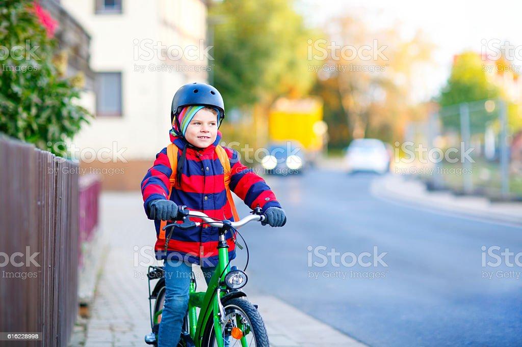 Little kid boy in helmet riding with bicycle through city - Foto de stock de Accesorio de cabeza libre de derechos