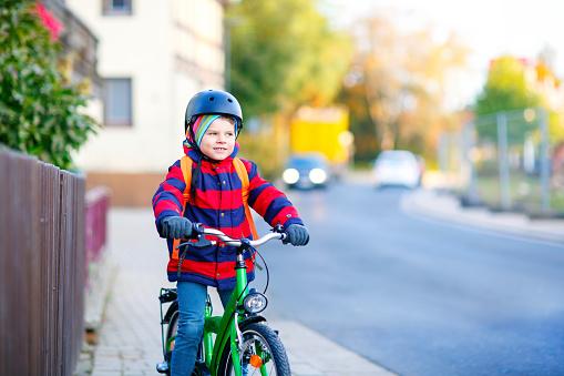 Little Kid Boy In Helmet Riding With Bicycle Through City Foto de stock y más banco de imágenes de Accesorio de cabeza